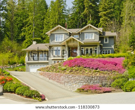 Big custom made luxury house on the rocky slope with nicely landscaped front yard in the suburbs of North Vancouver, Canada.