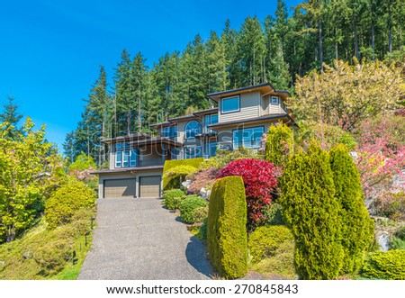 Big custom made luxury house with nicely landscaped front yard and  driveway to the garage in the suburb of Vancouver, Canada.