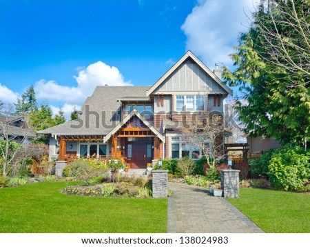 Big custom made luxury house with nicely paved long doorway and trimmed front yard in the suburbs of Vancouver, Canada.