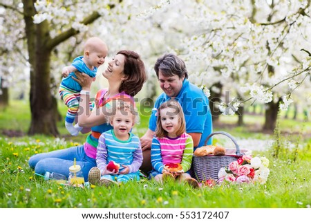 Big family with three little children eating lunch outdoors. Parents and kids with picnic basket in spring garden. Mother, father, preschooler girl, toddler boy and baby eat and drink in summer park.