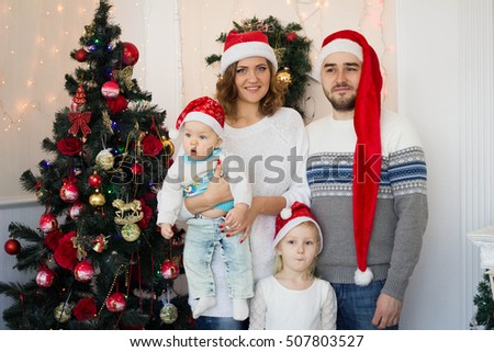 big happy family sitting in Santas caps near the Christmas tree