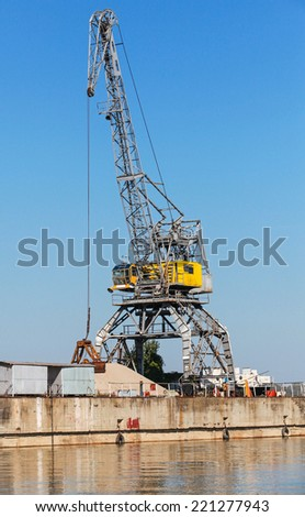Big industrial harbor crane works on the river coast in Bulgarian port