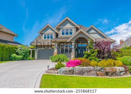 Big luxury custom made house with nicely landscaped front yard and driveway to garage in the suburb of Vancouver, Canada.