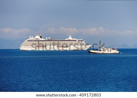 Big ocean cruise liner and a smaller vessel at blue sea tropical background.