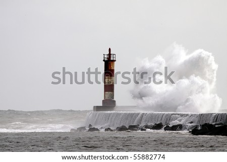 Big wave against lighthouse in the north of Portugal