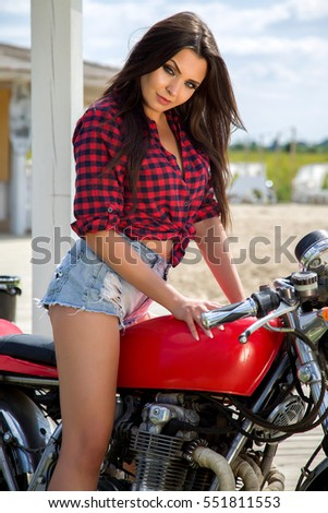 Biker Girl on Retro Motorcycle - Portrait of a cool woman on a vintage motorbike