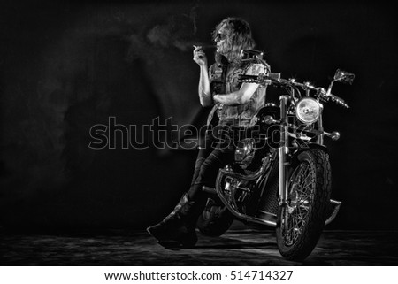 Biker smoke standing near a motorcycle.