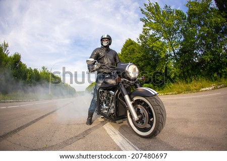 biker staying with unknown big chopper bike on road with smoke of the tire