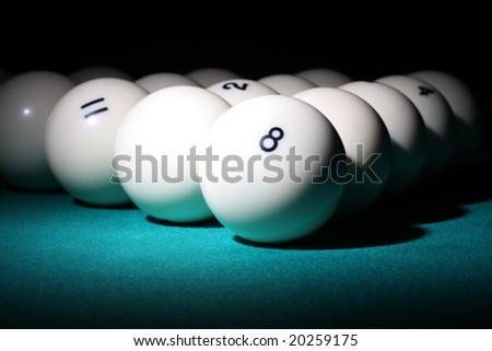 "Billiard. Balls pyramid with number 8 ball on a foreground. Selective focus on a 8ball. ""Low-key"" scene."