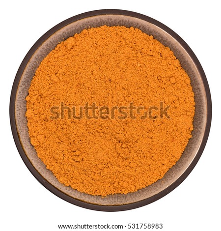 Bio organic cayenne powder in ceramic bowl isolated on white background, top view