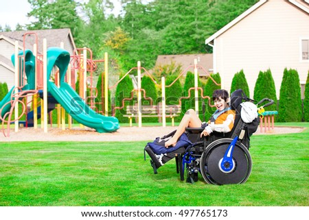 Biracial ten year old disabled boy in wheelchair sitting at a park by a playground, smiling in chair