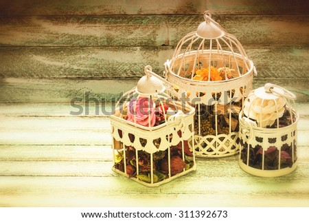 Bird cage decor on wooden background, vintage effect filter