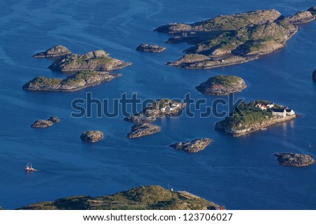 Bird eye view of fishing boats sailing between scenic islets near Henningsvaer on Lofoten islands in Norway
