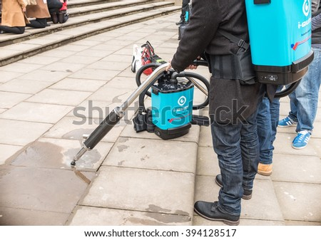 BIRMINGHAM, UK - MARCH 5 2016: A Birmingham City Council man works with an anti-chewing gum mark machine on the ground