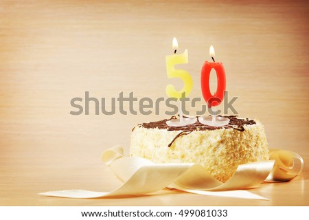 Birthday cake with burning candle as a number fifty. Focus on the candle