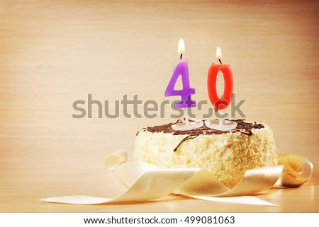 Birthday cake with burning candle as a number forty. Focus on the candle