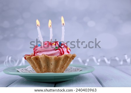 Birthday cup cake with candles on plate on color wooden table and light background