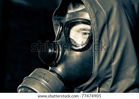 Bizarre portrait of man in gas mask on smoky industrial background with pipes after nuclear disaster