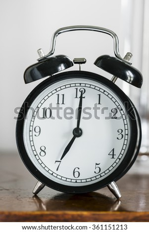 black alarm clock showing 7 o'clock on a bedside table
