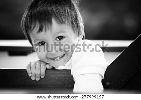 Black and white close portrait of happy little boy, outdoor