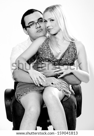 Black and white closeup portrait of handsome man holding girl on legs and hugging her