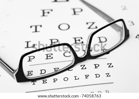 Black and white glasses on a eye sight test chart. Isolated on white background.