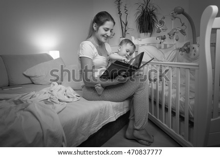 Black and white image of young mother reading book to her baby son before going to bed
