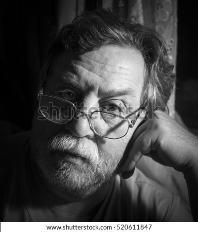 "Black and white monochrome photo. Portrait of a sad adult man with a gray mustache. ""Real People"" series"