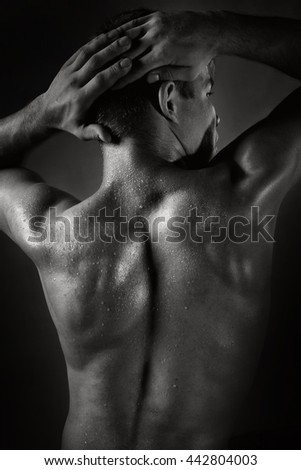 Black and white photo, a brutal man posing in the studio with a naked back, water droplets on the skin.