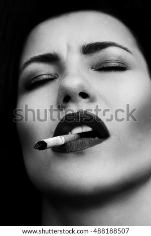Black and white photo of a beautiful girl with sigarette. Smoke girl