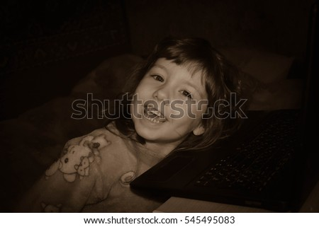 black and white photo of a little girl with a laptop