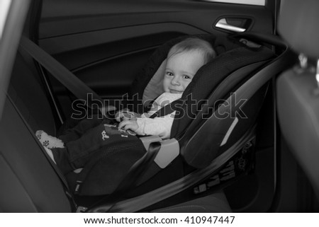 Black and white photo of little baby on back seat