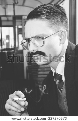 black  and white photo of man with glasses and whiskers  in a suit sitting in an old wooden wagon train and smoking a cigar, retro vintage fashion style