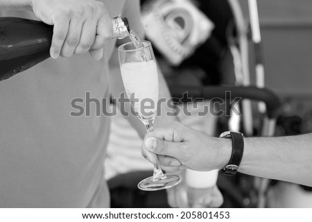 Black and white photo of people holding glasses with champagne at a party
