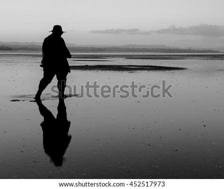 Black and white photo of silhouette woman walking alone