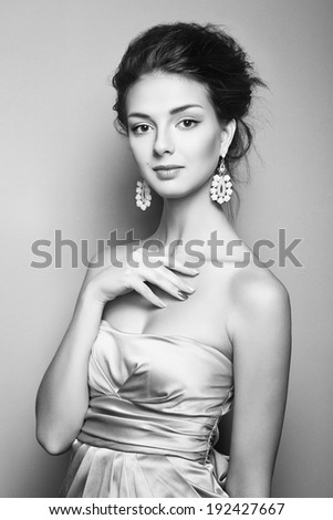 Black and white portrait of beautiful woman model with fresh makeup and romantic  hairstyle. Beauty girl with professional makeup. Jewelry. Creative nails. Fashion photo