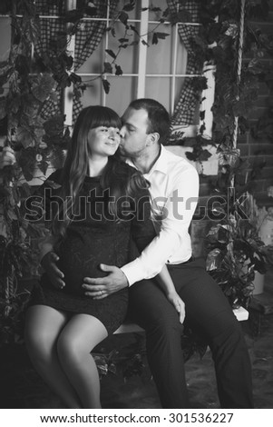 Black and white portrait of handsome man hugging pregnant wife on swing