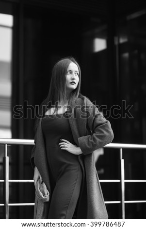 Black and white portrait of stylish business woman in urban city