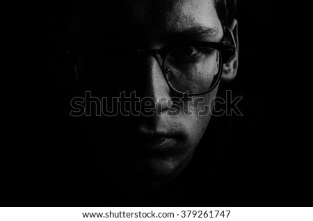 Black and white portrait of the young man in glasses in low key