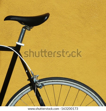 Black bicycle against a yellow wall