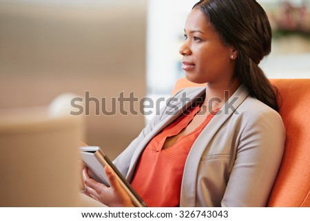 Black Businesswoman working on digital tablet in hotel lobby