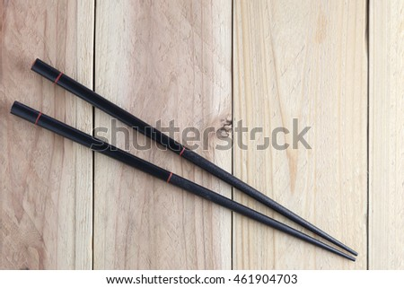 Black chopsticks spoon on wood floor for the design food concept background.