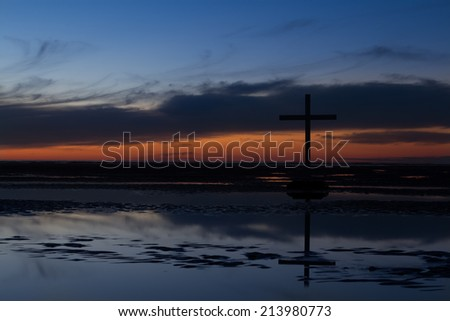 Black cross at low tide on a beach as the sunsets.