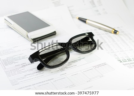 Black glass with a pen and smartphone on finance document background