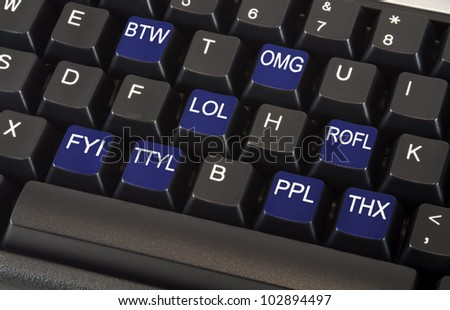 Black keyboard with text message slang words on keys for Rofl meaning in text