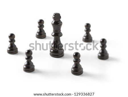 Black king chess piece floored in the midst of a ring of black pawns, lacking one.