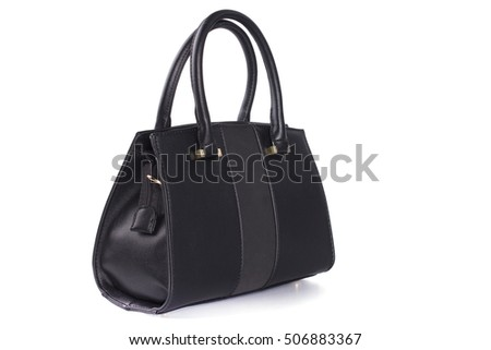 Black leather bag is medium in size with short handles standing on a white background in the studio. She turned sideways.