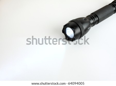 Black led flashlight on white white paper.