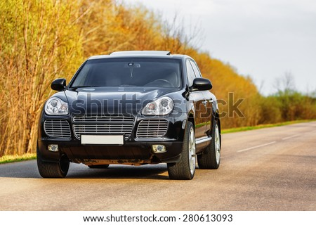 Black luxury car at byroad in autumn time