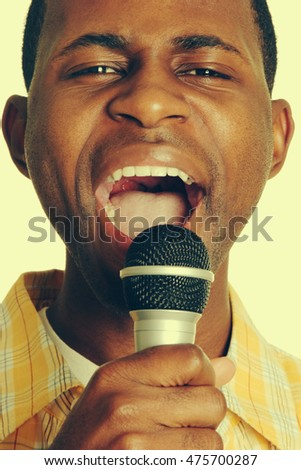 Black man singing into microphone